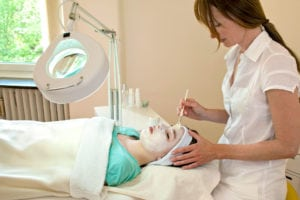 alternative practitioner applying a chemical peel to a female patient