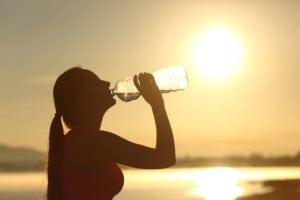 Woman in front of the sun drinking water